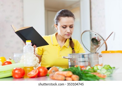 woman cooking  veggie food with cookbook at home kitchen