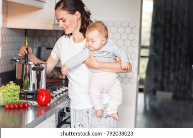 Woman cooking while holding six month old baby in her hands