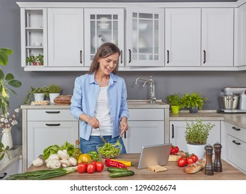 Woman cooking while watching the digital tablet
