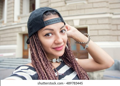 Woman with cornrows dreads making selfie at the street
