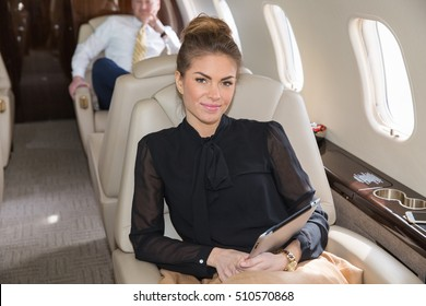 woman in corporate jet looking to camera - airline business shooting