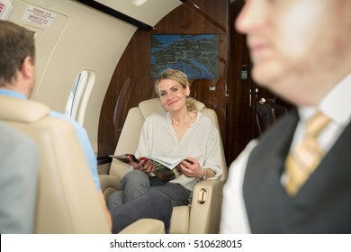 woman in corporate jet relaxing and reading a magazine