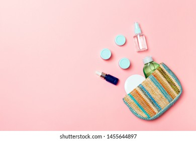 Woman cosmetic bag with set of beauty product and bodycare cream on pink pastelbackground with copy space for you design.