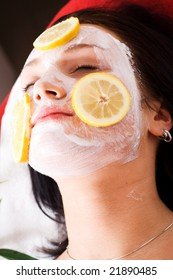 The woman in the cosmetic lounge with the mask and fruit on the face.