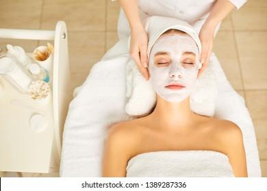 Woman in cosmetic mask lying down in the beauty salon.