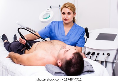 woman cosmetician performing hardware body treatment to male client in cosmetological clinic