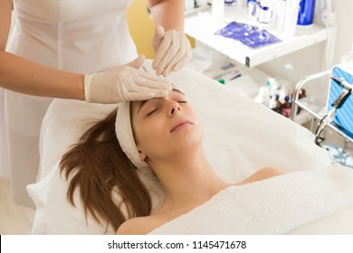 woman cosmetology procedure with girl  black face mask
