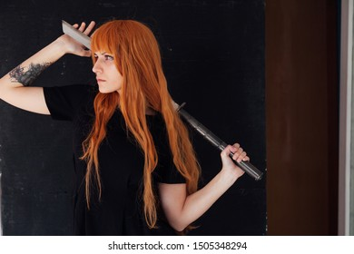 Woman cosplayer anime with red hair holds a Japanese sword