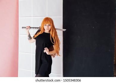 Woman cosplayer with red hair holds Japanese sword