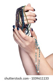Woman with costume jewelery beads. Female fingers with shiny blue nails manicure. Girl's hands with bijouterie isolated on white background