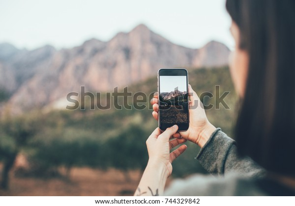 Woman in cosy warm sweater uses smartphone to make photograph of beautiful nature and mountains in park, to share on social media channels to show to friends and family