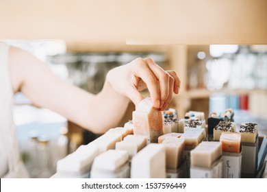 Woman with cotton bag buying personal hygiene items in zero waste shop. Eco Organic Cosmetics. Girl choose toiletries products in plastic free store. Minimalist lifestyle. Shopping at local businesses