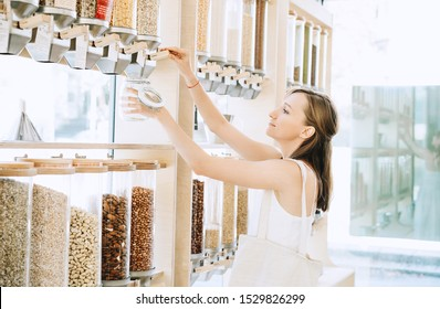Woman with cotton bag and glass jar buying in zero waste shop. Dispensers for cereals, grains, nuts in plastic free grocery store. Sustainable shopping at small local businesses. Eco Bio Organic Food