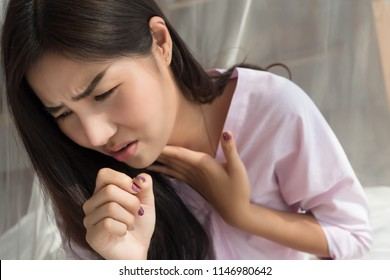 woman coughing; portrait of woman suffering from cold, flu, sore throat sickness with cough symptoms; female inspiratory body care, inspiration or lung sickness concept; asian young adult woman model