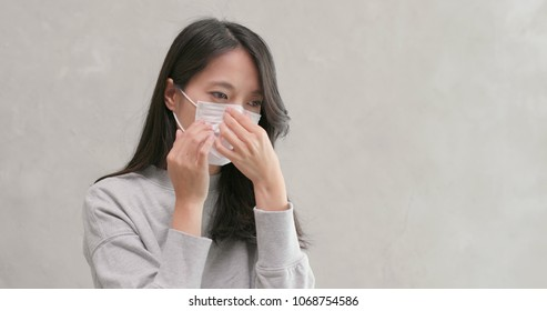 Woman coughing and wearing face mask
