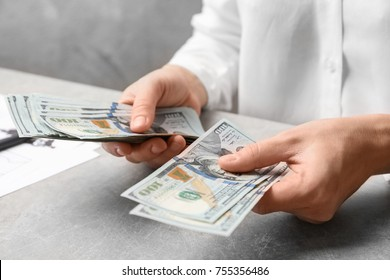 Woman counting dollars at table