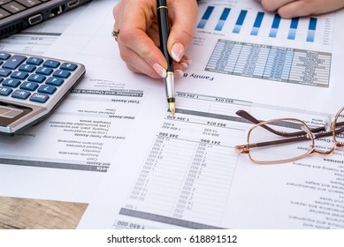 woman counting financial data analyzing with calculator in office.