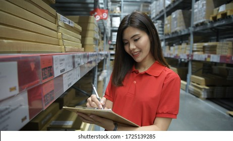 Woman counting the goods according to the document in the storage room.