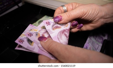 Woman counting Mexican pesos at a cash register
