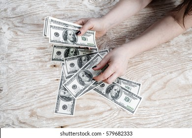 Woman counting money. Dollars in woman's hands. Many one hundred dollar bills in hands.