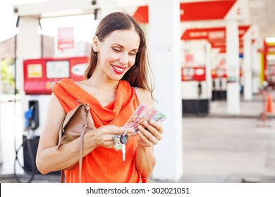 woman counting money on a gas station