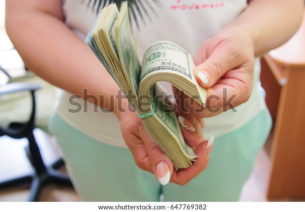 woman counting stack of money in her hands