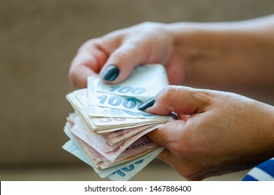 The woman is counting turkish liras banknote