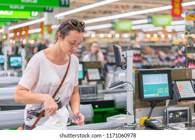 The woman counts on the checkout in the supermarket
