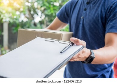 woman courier holding a parcel Shipping Mail appending signature signing delivery note after receiving package from delivery man