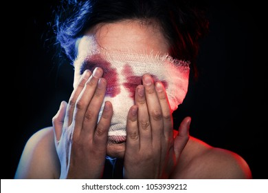 woman cover bandaged bleeding eyes on black background
