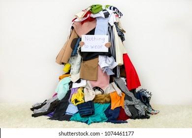 Woman covered with pile of different cloth holding Nothing to wear table sign
