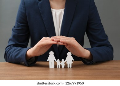 Woman covering cutout paper family at table, closeup. Life insurance concept