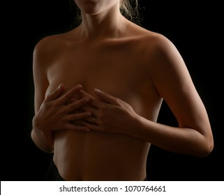 Woman covering her breast on dark background.