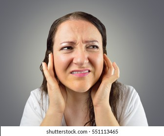 woman covering her ears with her hands isolated on a gray background