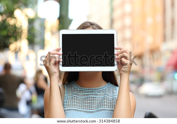 Woman covering her face with a blank tablet screen showing display