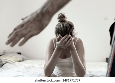 Woman covering her face in fear of domestic violence. Terrible domestic violence in family. Woman victim of domestic violence and abuse. Woman is covering her face with fear. Young couple in problems