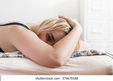 Woman covering her face in grief, lying on a bed in bedroom