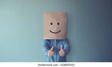 Woman covering her face with a smiling face emoticon, copy space.