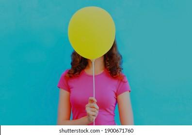 Frau, die ihren Kopf mit gelbem Ballon auf buntem blauem Hintergrund bedeckt