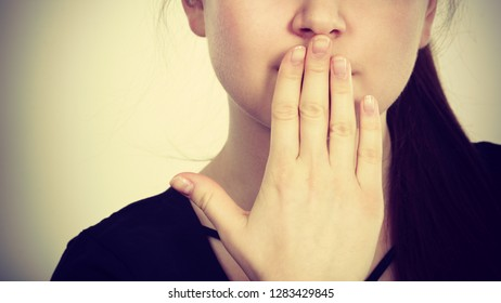 Woman covering her mouth with hand. Seeing something shocking, surprised and speechless face expression.