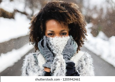 Woman covering her mouth with wool warm scarf under the snow in cold winter.