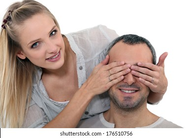 Woman covering a man's eyes