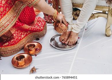 Woman covers groom's feet with a water during Hindu wedding ceremony Saptapadi