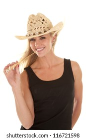 A woman in a cowboy hat and a black tank top has a piece of wheat in her mouth and smiling.