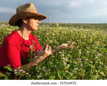 A woman in a cowboy hat in a field of blooming buckwheat.