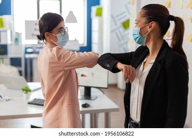 Woman coworkers touching elbow wearing face mask in new normal office during global pandemic with covid19 flu keeping social distancing as prevention to avoid infection.
