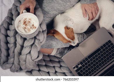 Woman in cozy home clothes relaxing at home, drinking cacao, using laptop, top view. Comfy lifestyle.