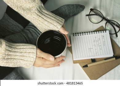 Woman in a cozy sweater holding a cup of hot drinks, Working and reading a book in a lazy day, Winter morning at home in bed, Feeling warm concept. (Color processed)