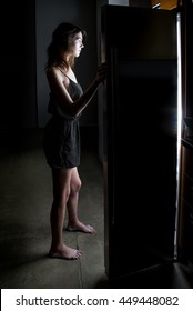 Woman craving and looking for food in an empty frige late at night.  The image is shot low key to depict night time.