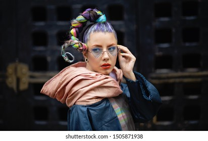 Woman with crazy dreadlocks, eyeglasses and piercings - Edgy girl on streets with avant-garde fashion style
